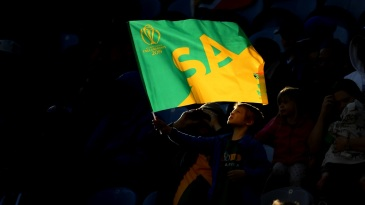 A young South Africa fan waves a flag in support of his country