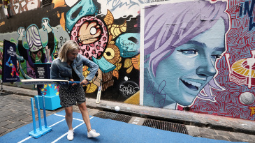 Ellyse Perry bats in front of a T20 World Cup mural featuring her in Melbourne