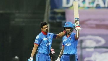 Shikhar Dhawan raises his bat as Shreyas Iyer pats on his back