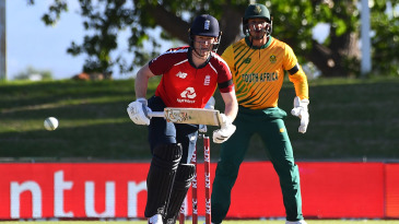 Eoin Morgan watches the ball after playing a shot as Quinton de Kock looks on