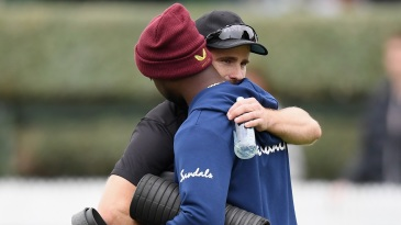 Kemar Roach, seen here getting a hug from Kane Williamson, lost his father in the 48 hours before the match