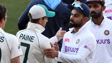 Tim Paine and Virat Kohli catch up after the game