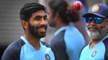 Jasprit Bumrah smiles as he tosses a new red ball