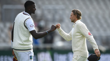 Jason Holder and Joe Root fist-bump each other