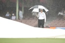 Reserve umpire Claire Polosak watches on as ground staff cover the pitch during a rain delay, Australia vs India, 3rd Test, Sydney, 1st day, January 7, 2021