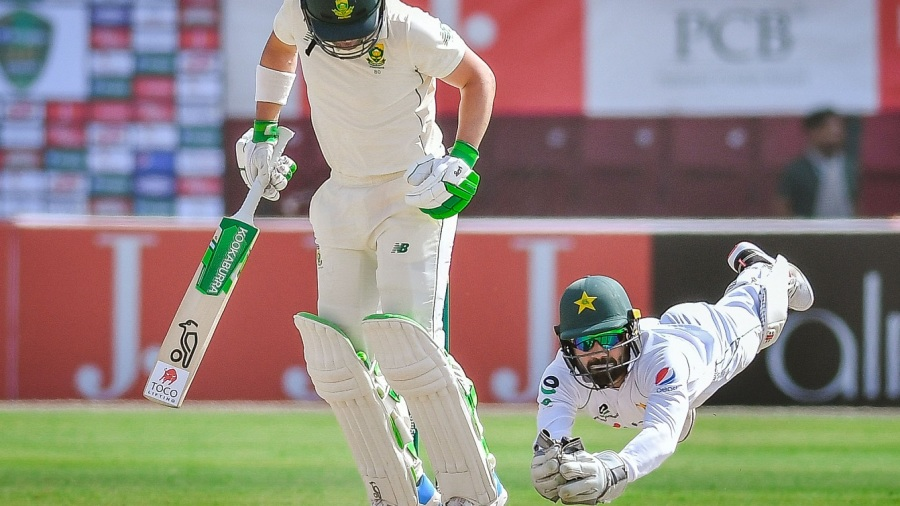Mohammad Rizwan takes a diving catch to send Dean Elgar back