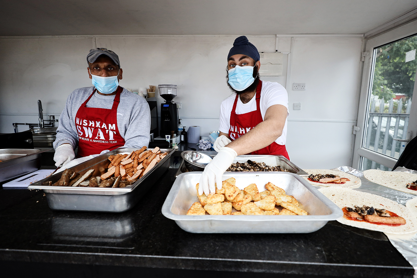 Surrey's Amar Virdi (right) cooks food in a Southall kitchen to feed the homeless
