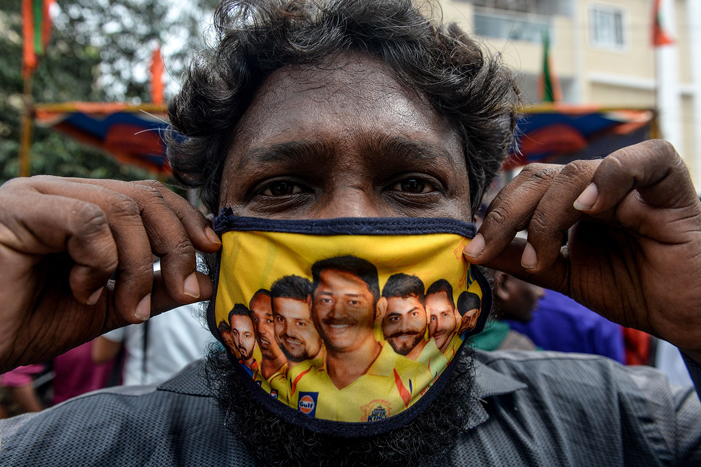 A man wears a mask featuring MS Dhoni and other Chennai Super Kings players