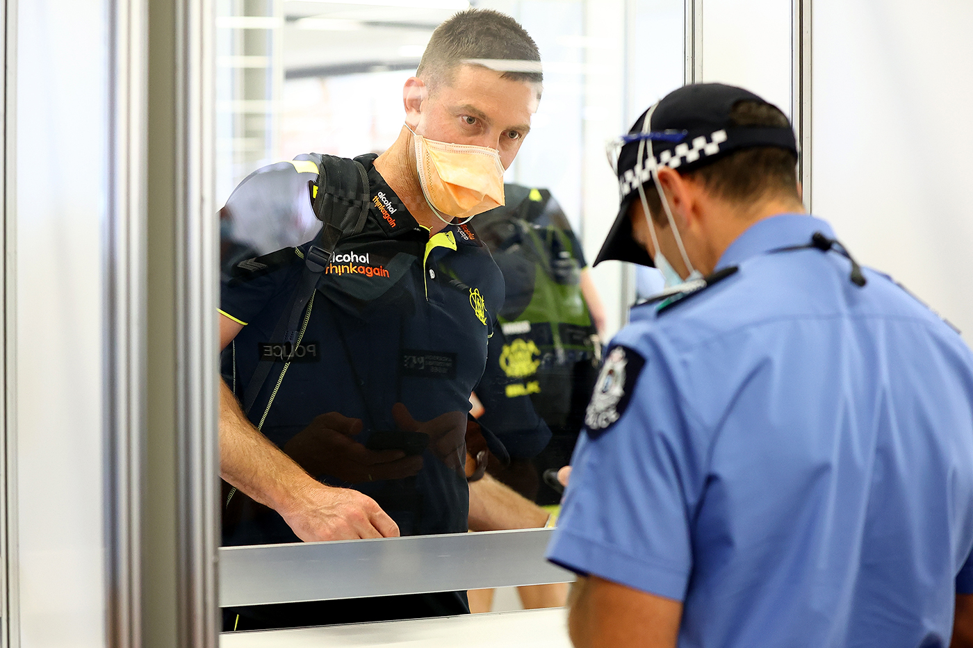 Shaun Marsh has his documents inspected at Perth airport after taking a flight from Adelaide