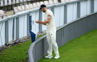 Mark Wood sanitises his hands
