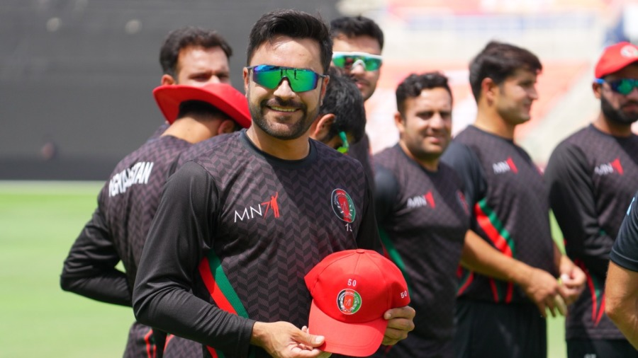 Rashid Khan poses with a special cap gifted to him on the occasion of his 50th T20I appearance