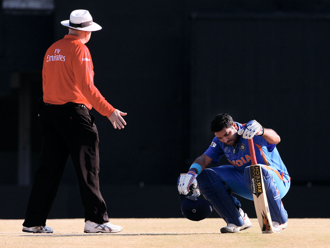Umpire Steve Davis checks on a dehydrated and heat-exhausted Yuvraj Singh during India's game against West Indies in Chennai