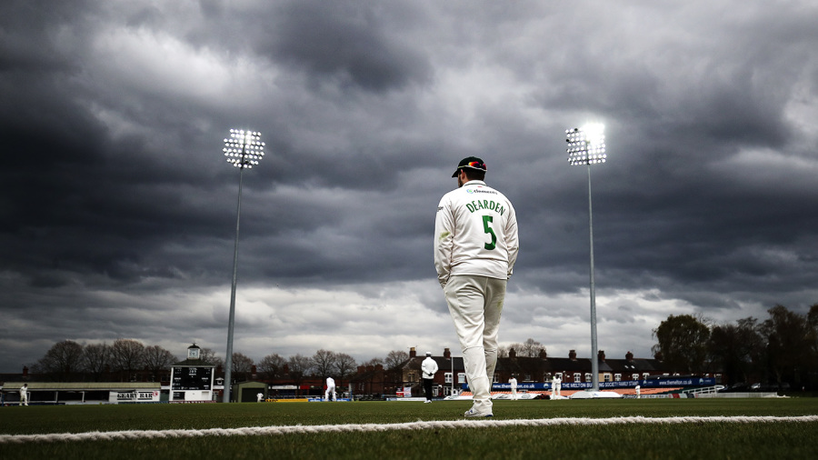 Leicestershire's Harry Dearden stands at the boundary with his hands in his pockets as dark clouds gather in the sky
