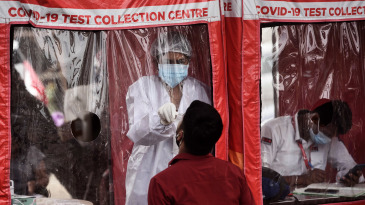 A healthcare worker collects swab samples of people at a Covid-19 test collection centre in Goregaon