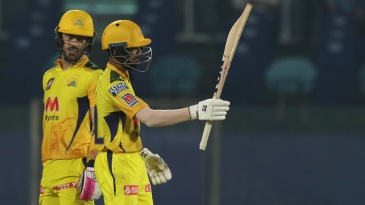 Ruturaj Gaikwad raises his bat after getting to fifty as Faf du Plessis looks on