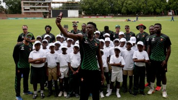 Blessing Muzarabani takes a selfie of players and local school children