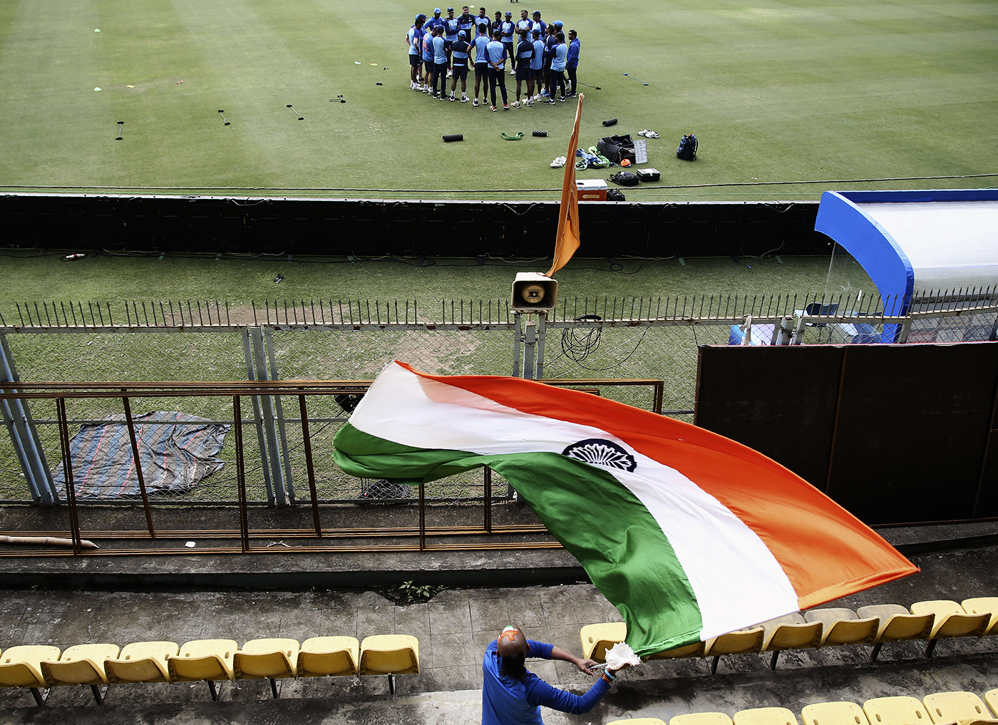Sudhir Gautam waves an India flag while India players get into a huddle
