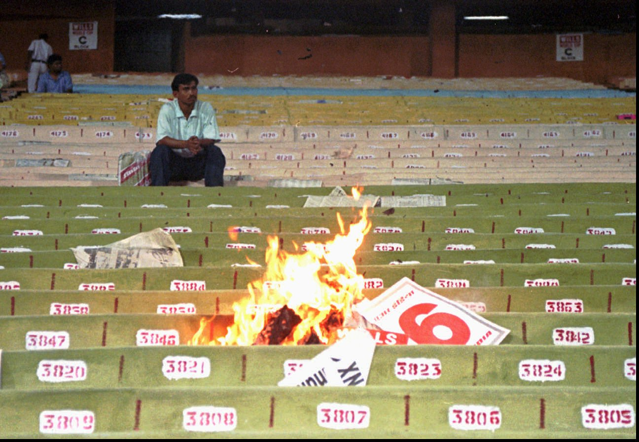 A lone fan contemplates his life choices as the match goes up in flames around him
