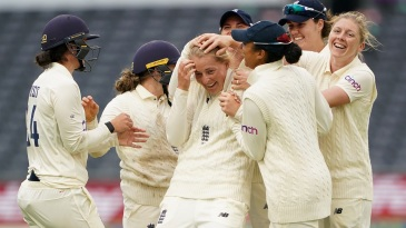 Sophie Ecclestone is mobbed by her team-mates after picking up a wicket