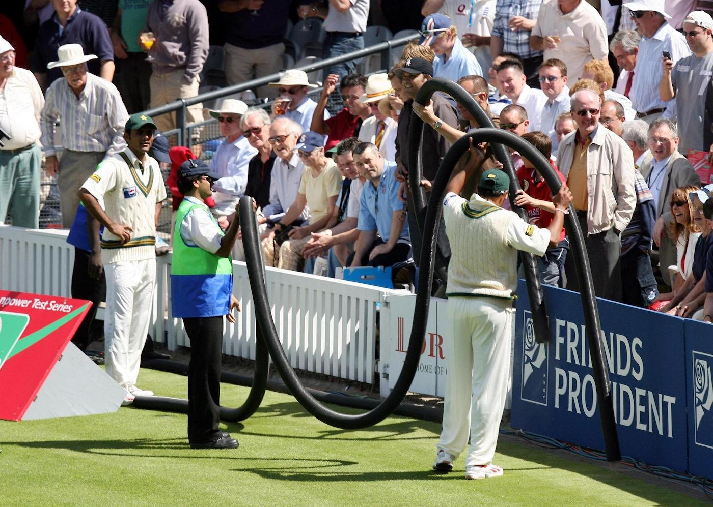 Danish Kaneria enlists the help of spectators to flush the ball out of a watering hose
