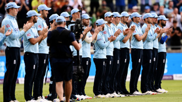 The players and officials line up in remembrance of Bob Willis, on #BlueforBob Day at Edgbaston
