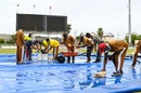 The ground staff at Sabina Park mop up water from the covers, West Indies vs Pakistan, 2nd Test, Jamaica, 2nd day, August 21, 2021