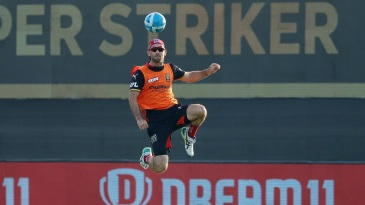 Glenn Maxwell plays with a football during warm-up
