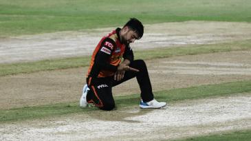 Rashid Khan kneels on the pitch