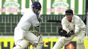 Kumar Sangakkara cuts a ball as Andy Flower looks on