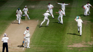 England's players mob Steve Harmison after he took the final wicket in dramatic style