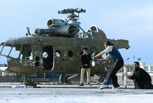 A group of Afghans play cricket in front of a destroyed helicopter, Kabul, March 17, 2005