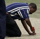 Groundman Wilson Ngoeese unrepairs a section of the pitch that had been illegally repaired overnight