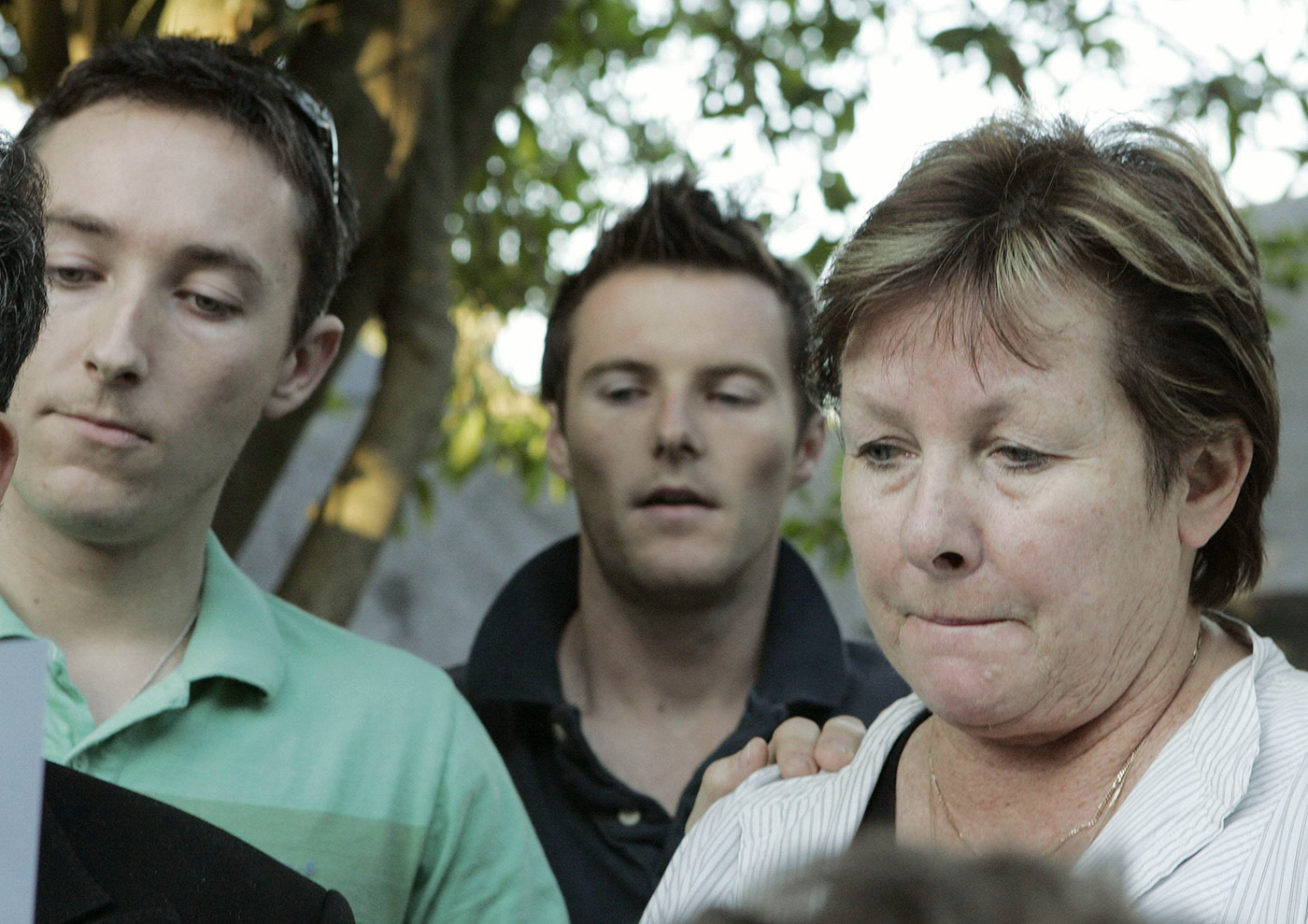 Gill Woolmer and her sons Russell and Dale listen to a statement about the death in Cape Town
