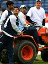 Mahendra Singh Dhoni gets behind a tractor in the company of Piyush Chawla and RP Singh