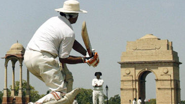 Young aspiring cricketers play on the lawns of India Gate