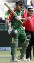 Junaid Siddique raises his bat after scoring fifty
