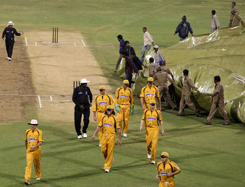 Groundsmen running to cover the pitch as the Australian Players walk off the field