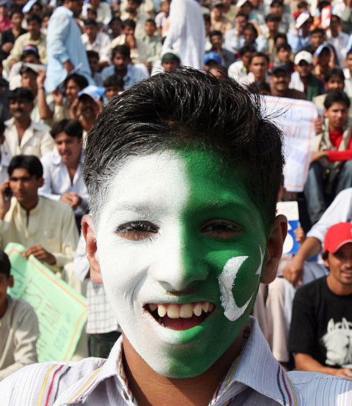 A fan with a face painted in the colours of the Pakistan flag