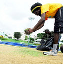 Groundstaff do some gardening on the pitch at the 3Ws Oval at the Cave Hill Campus of the University of the West Indies, Barbados, October 24, 2007