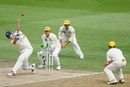 Cameron White heaves the ball to midwicket as Adam Gilchrist and Justin Langer look on