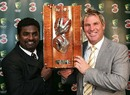 Muttiah Muralitharan and Shane Warne pose with the trophy named after them