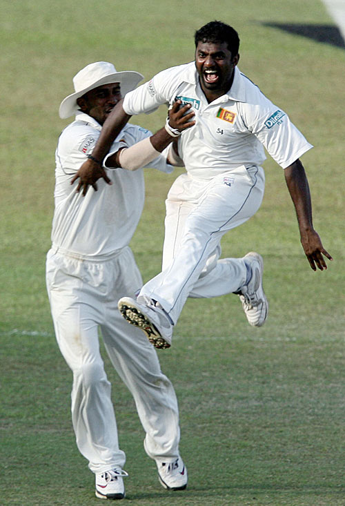 Muttiah Muralitharan is congratulated on the big wicket of Ian Bell