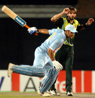 Mahendra Singh Dhoni makes his way past Shahid Afridi, India v Pakistan, Kitply Cup final, Mirpur, June 14, 2008