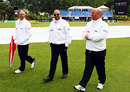Umpires Tony Hill, Amiesh Saheba and Mark Benson inspect the wet outfield