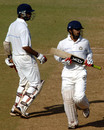 Cheteshwar Pujara and Shitanshu Kotak look on as the ball sails to the boundary