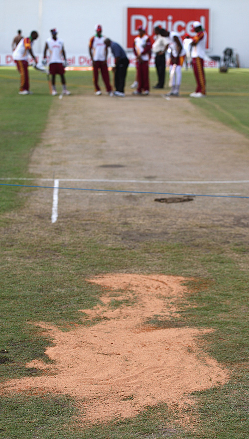 A drying agent (not sand...) is used to mop up excess water on the bowlers' run-ups