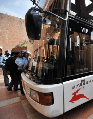 Security guards crowd round the Sri Lankan team's bullet-ridden bus, Lahore, March 3, 2009