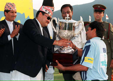 Crown Prince Dipendra of Nepal (C) gives the winner's cup to Indian captain Kapil Dev (R) in Kathmandu 09 May 1999 after the final of the Tempo World Legends Cup 1999.  The final cricket match between India and World XI saw India win by six wickets.