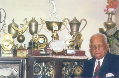 Mushtaq Ali in deep thought with his eyes closed as he sits in front of his numerous trophies