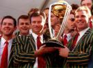 The rest of the Australian team look on as Steve Waugh and Shane Warne proudly display the World Cup trophy, 28 June 1999
